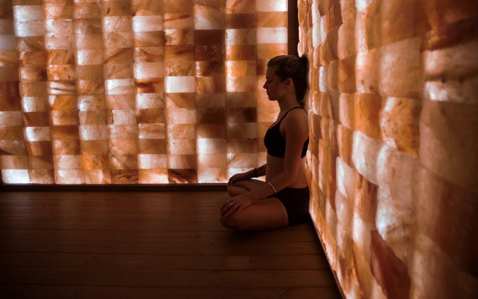 Woman meditating against the himalayan salt walls in WelPod