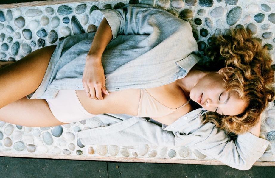 Woman laying on Circle Wellness Studios' riverstones