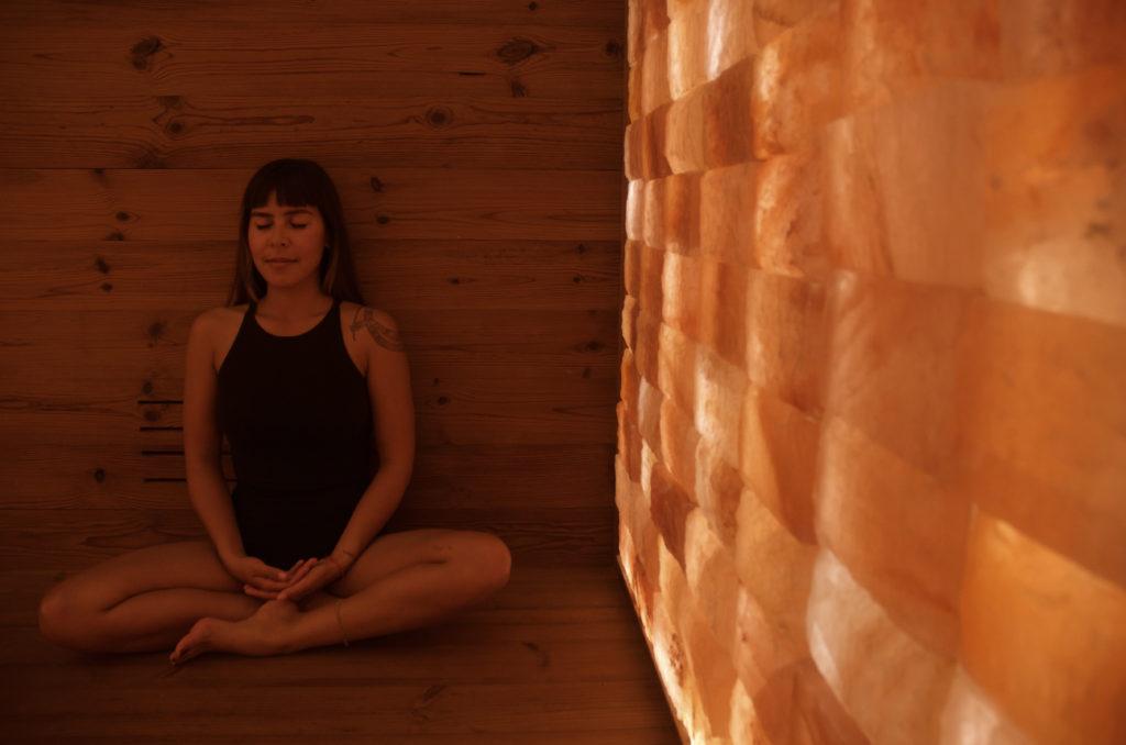 Woman sitting against wood wall in Circle Wellness Studios WelPod